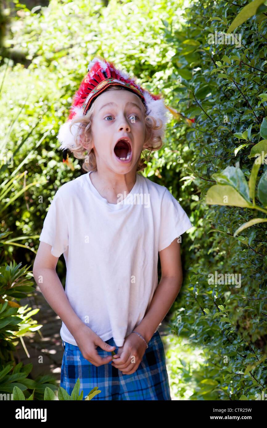 A blond boy wearing an toy Indian headdress. - Stock Image