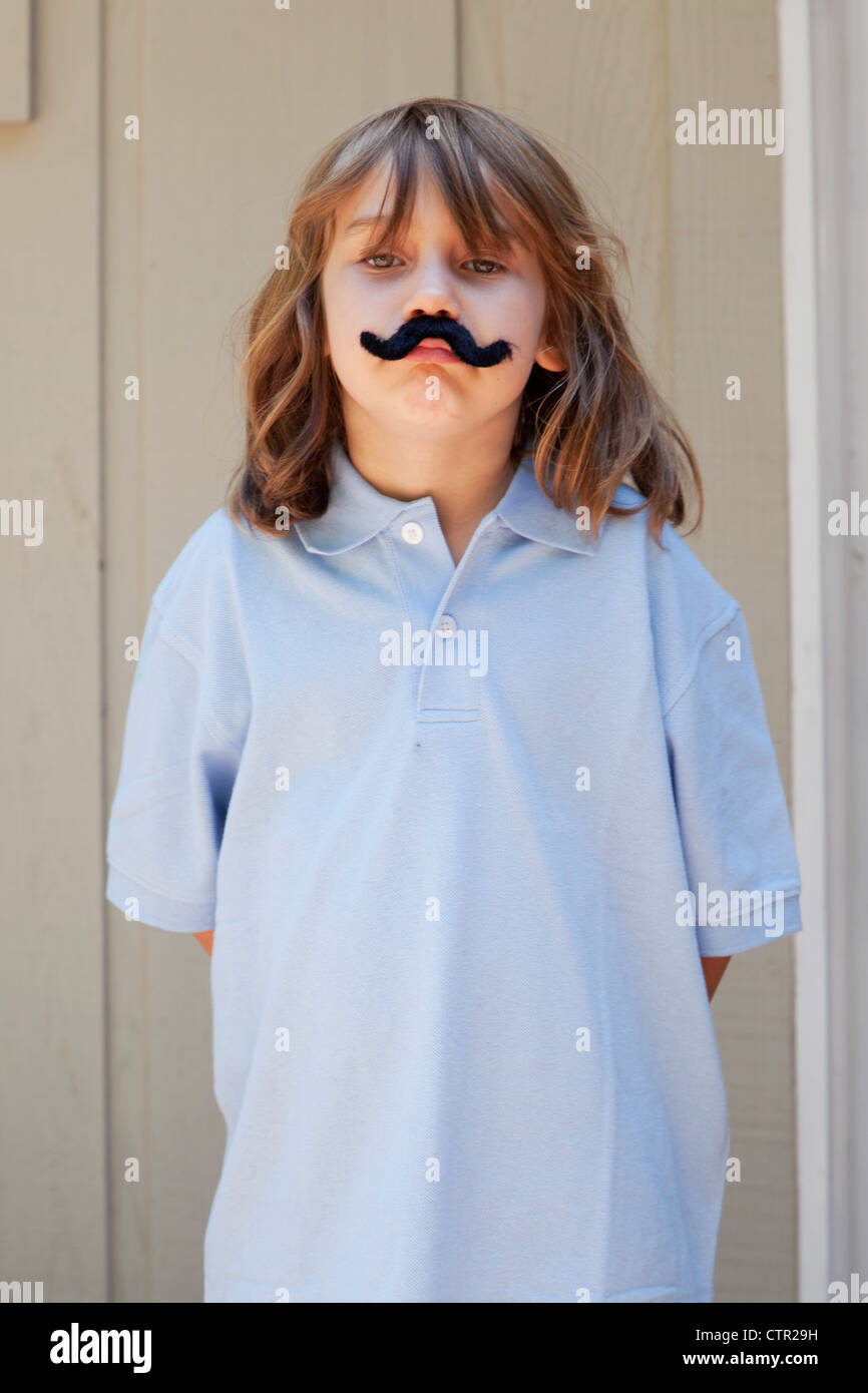 Little girl wearing a fake mustache. - Stock Image