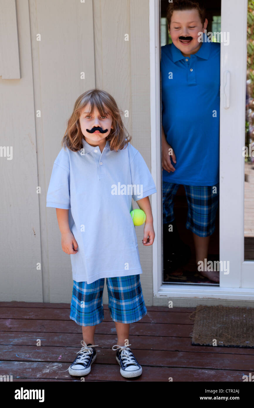 Little girl wearing a fake mustache, while her brother looks out of the door. - Stock Image