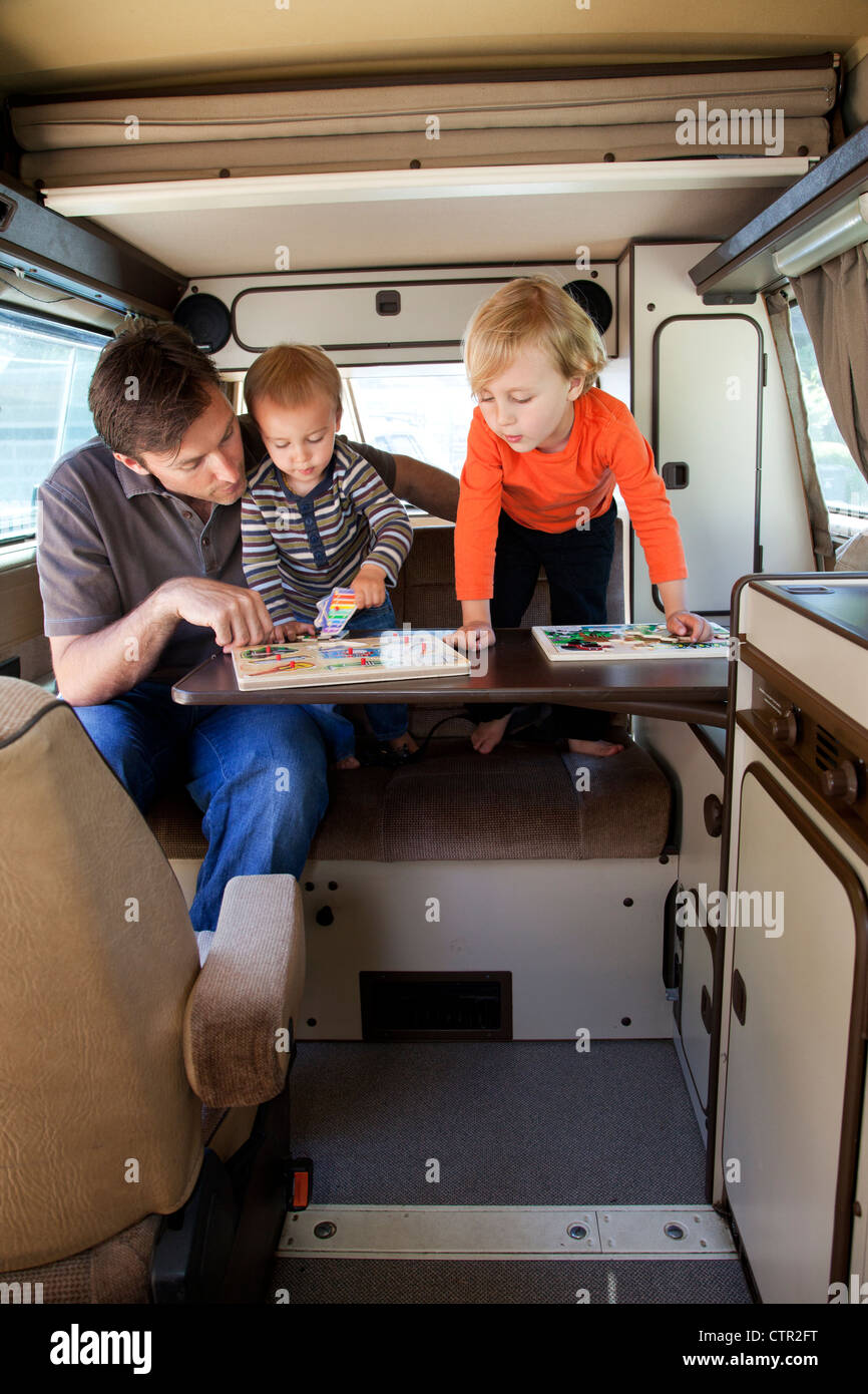 A father and his two sons are playing in the back of their camper trailer. - Stock Image