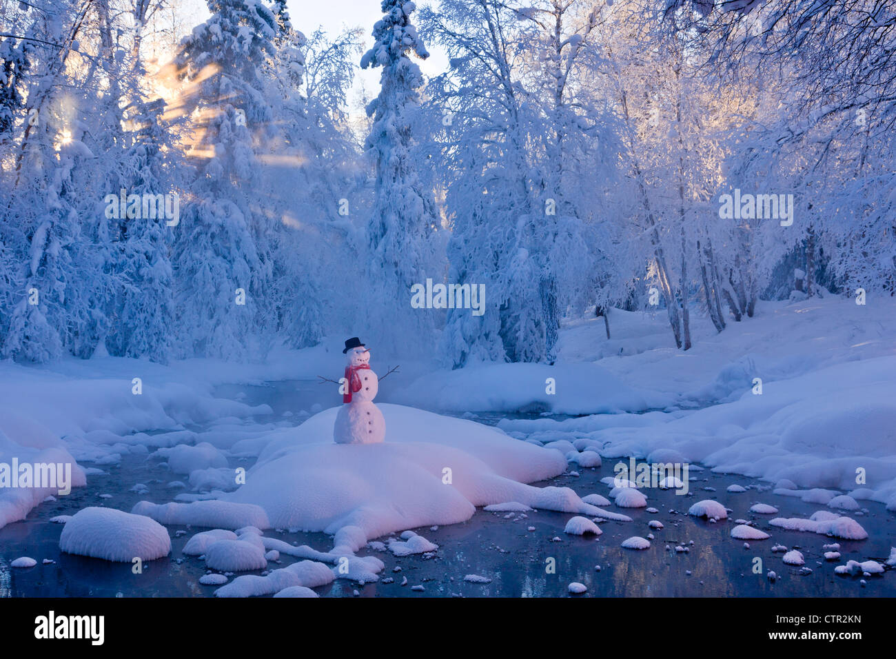 Snowman standing on small island in middle stream fog hoar frosted trees in background Russian Jack Springs Park - Stock Image