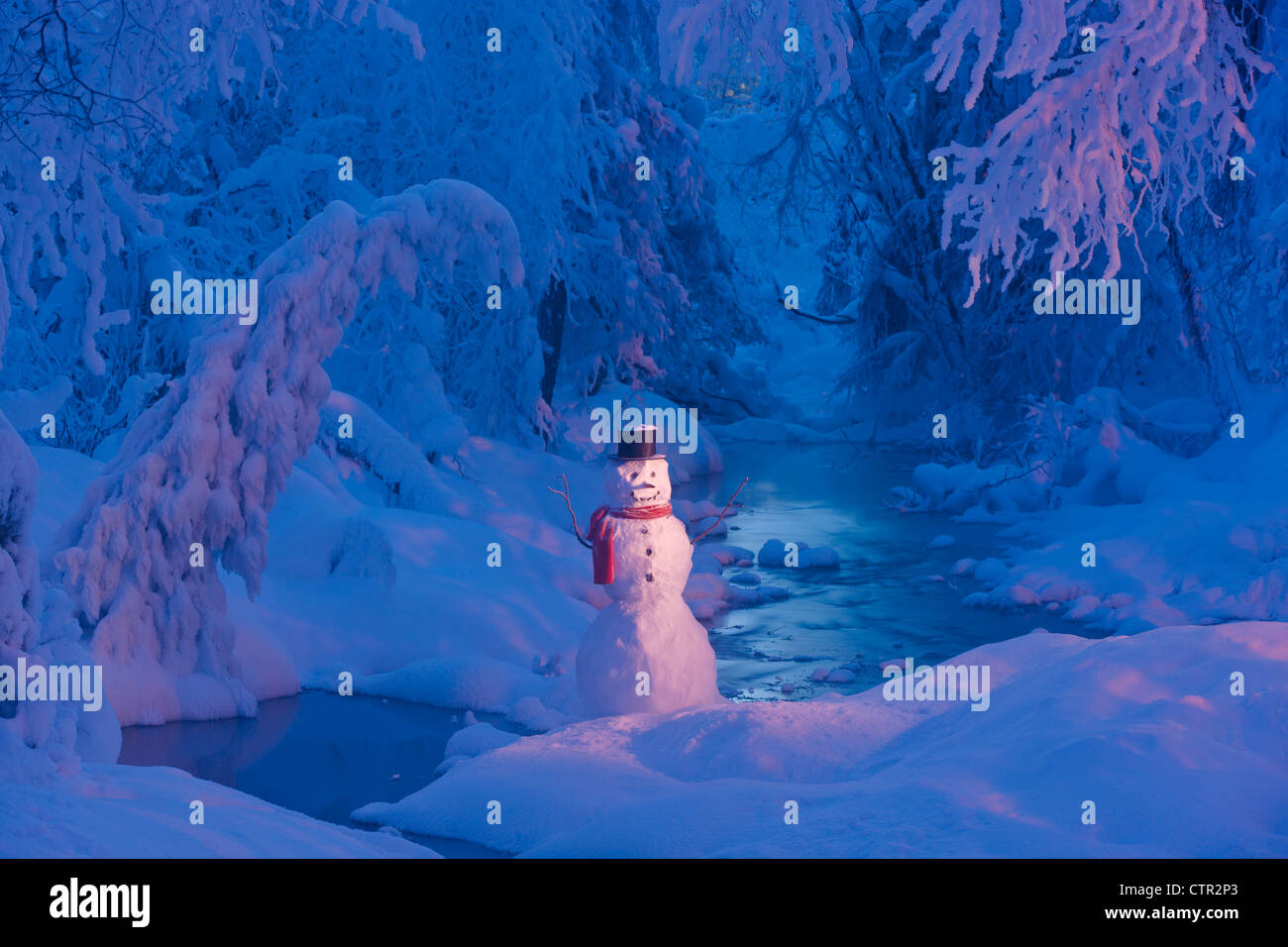 Snowman wearing black scarf top hat standing next small stream in hoarfrost covered forest twilight Russian Jack - Stock Image