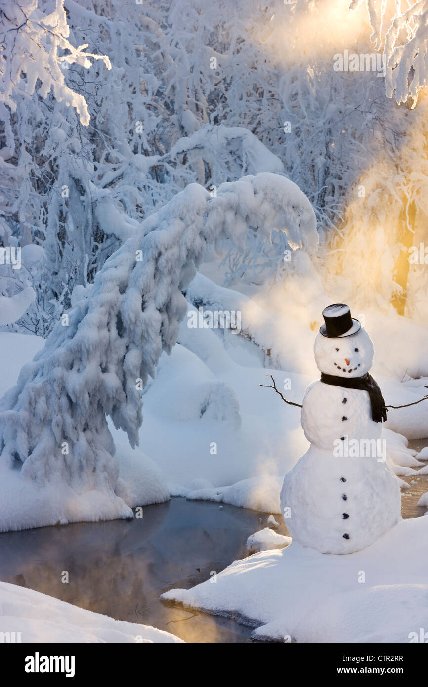 Snowman standing next stream sunrays shining through fog hoar frosted trees in background Russian Jack Springs Park - Stock Image