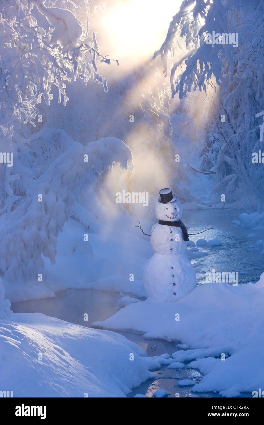 Snowman standing next stream sunrays shining through fog hoar frosted trees in background Russian Jack Springs Park Stock Photo