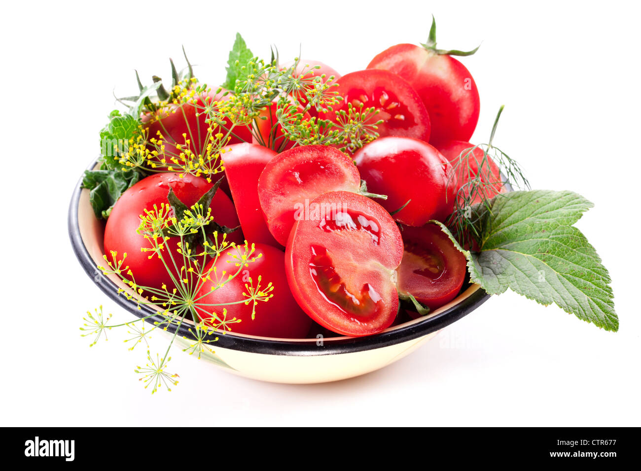 Tomatoes, cooked with herbs for the preservation on a white background. - Stock Image