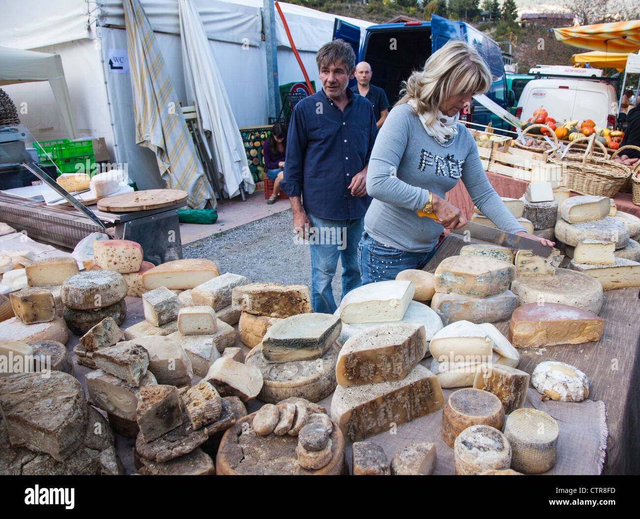 Market stall selling a variety of traditional mountain cheeses for sale in a market in rural Oulx, Piemonte, Italy - Stock Image