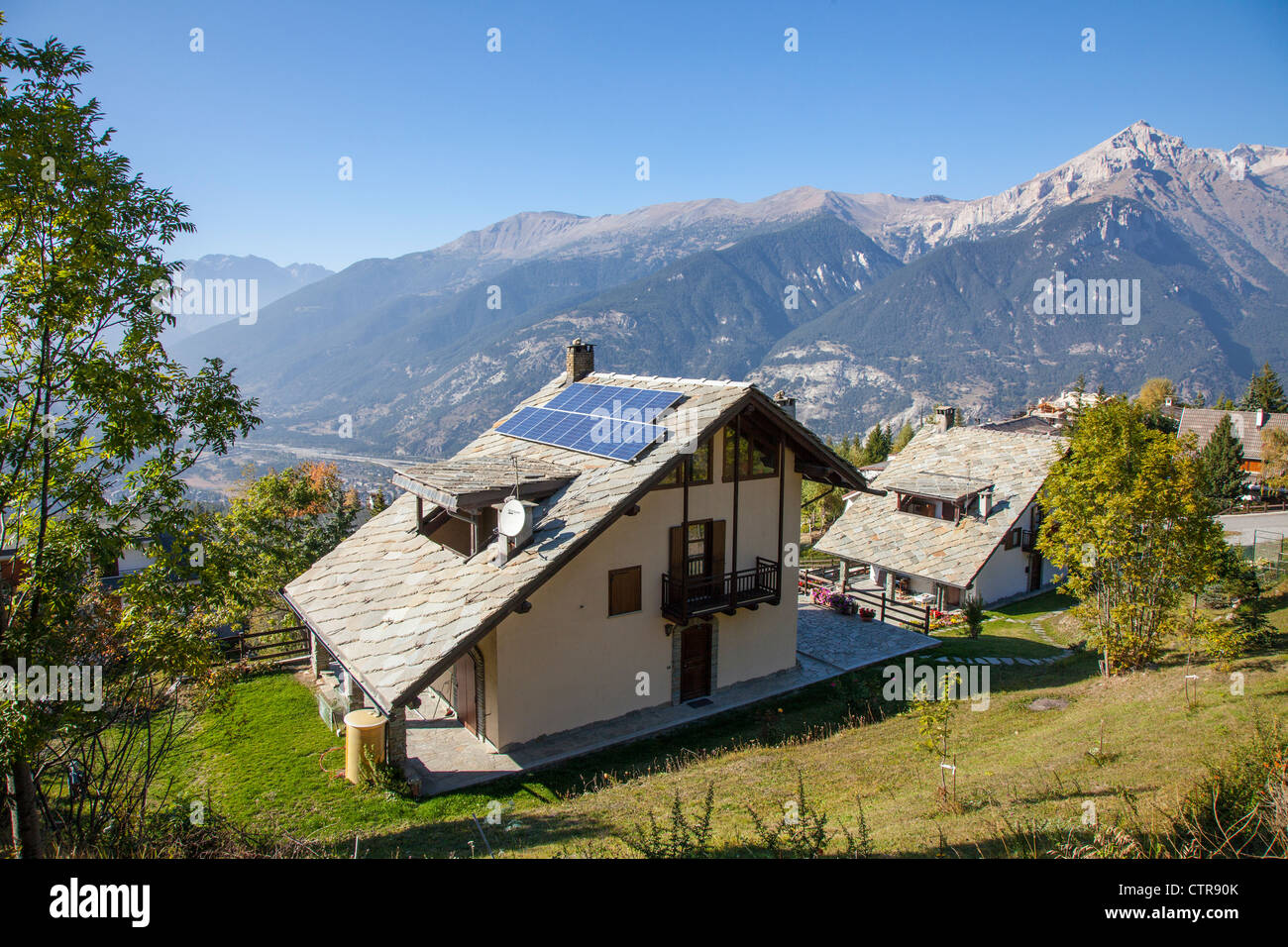Alpine house with solar panels in the ski resort of Sauze d'Oulx, Piemonte, Italy - Stock Image