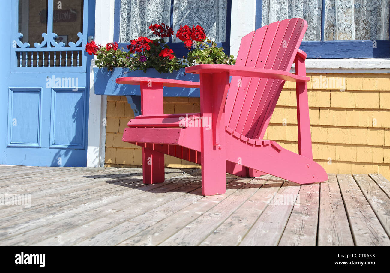 Colorful Adirondack chair sitting on a patio or deck with a window box full of geraniums. - Stock Image