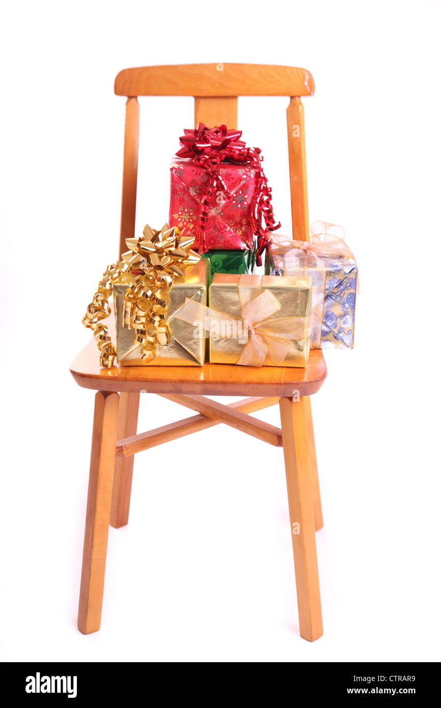Foil wrapped Christmas gifts stacked on a child's wooden chair. - Stock Image