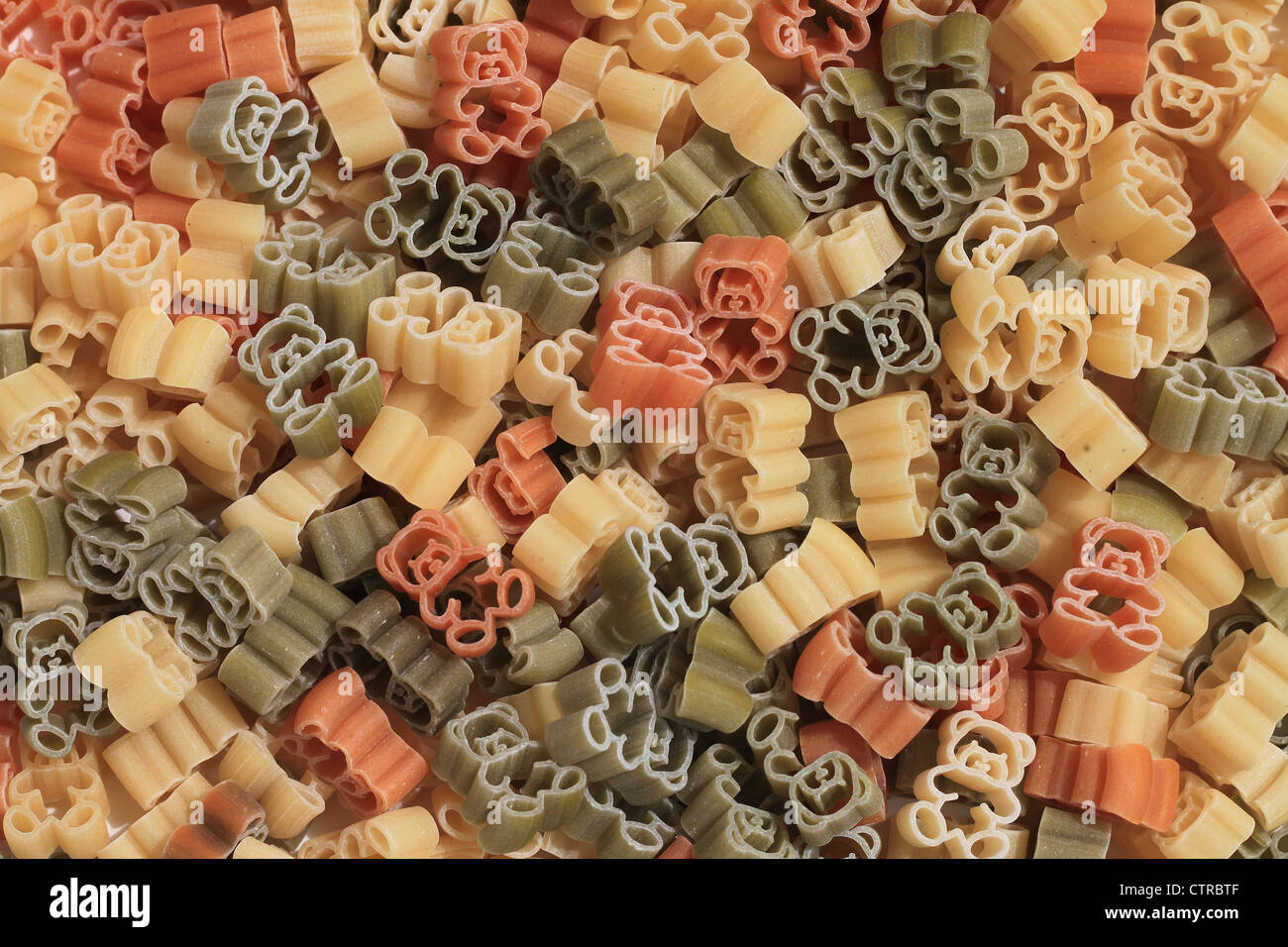 Italian pasta of durum wheat semolina with tomato and spinach in form of teddy bears. Funny for children. - Stock Image