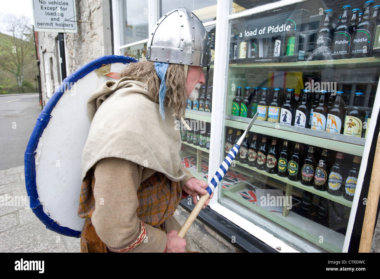 A man in Viking costume looking at bottles of beer in an off licence. - Stock Image