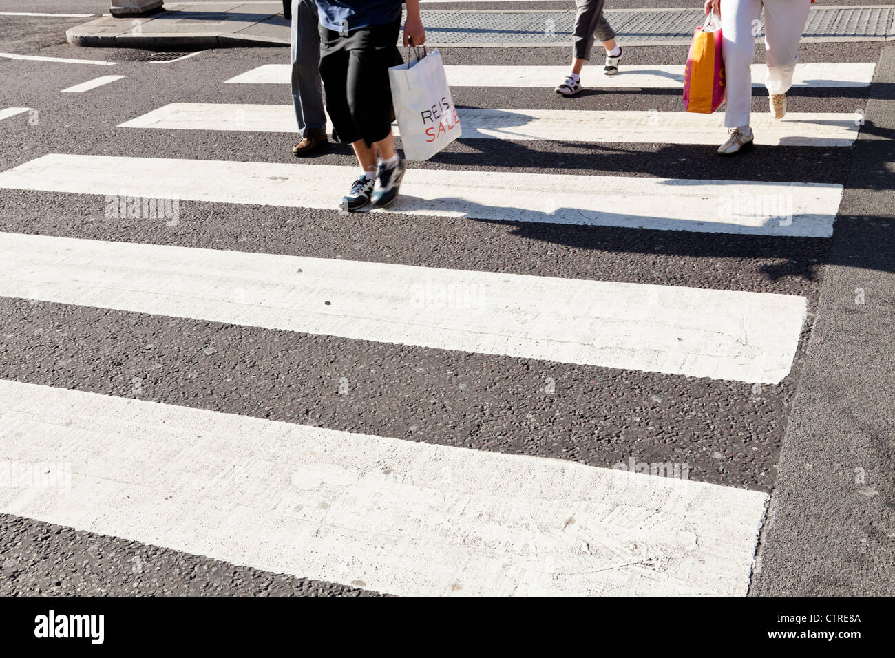 People crossing the road on a zebra crossing, England, UK Stock Photo