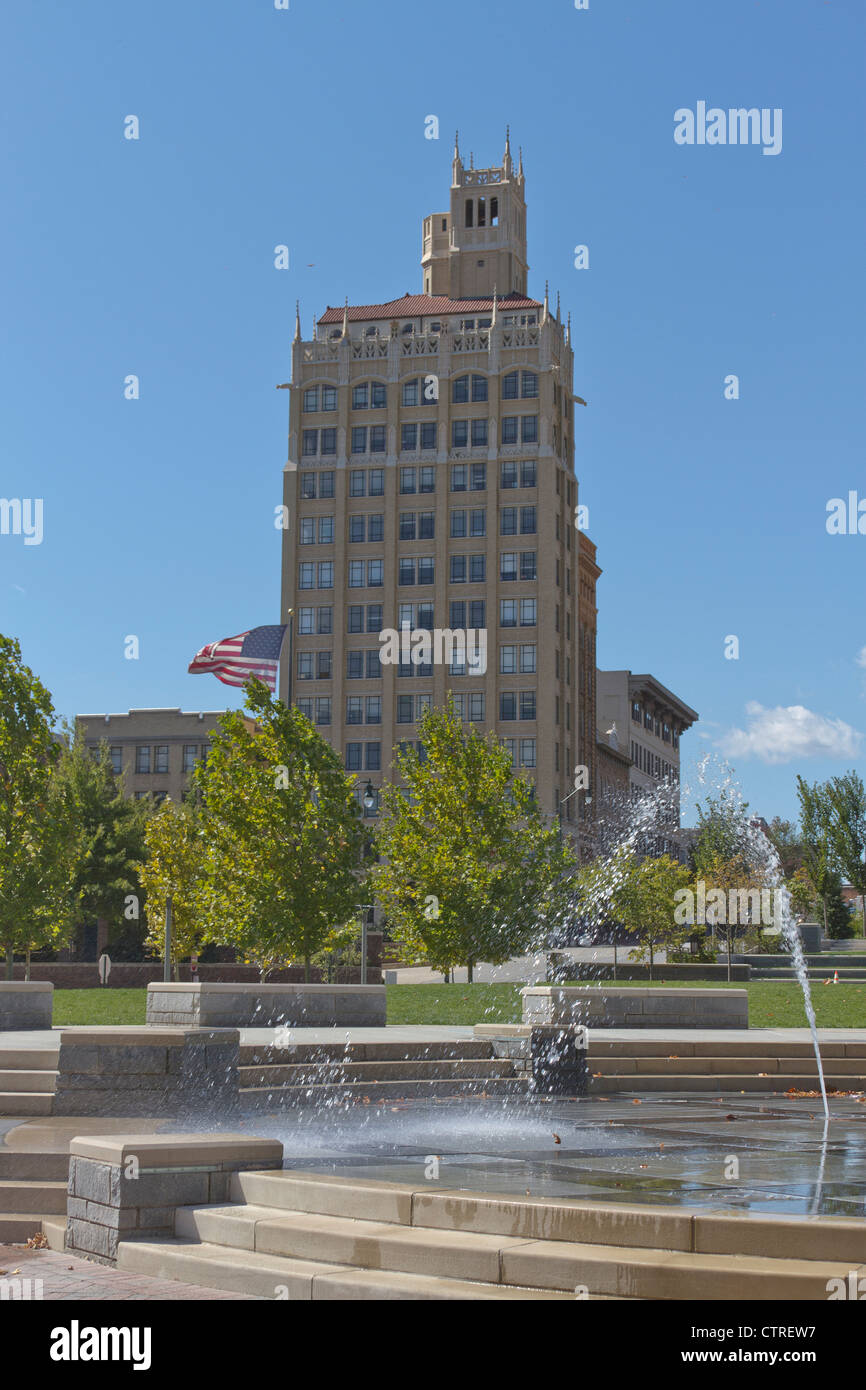 Downtown Asheville, North Carolina with an old art deco building and fountain in Pack Square in the foreground - Stock Image