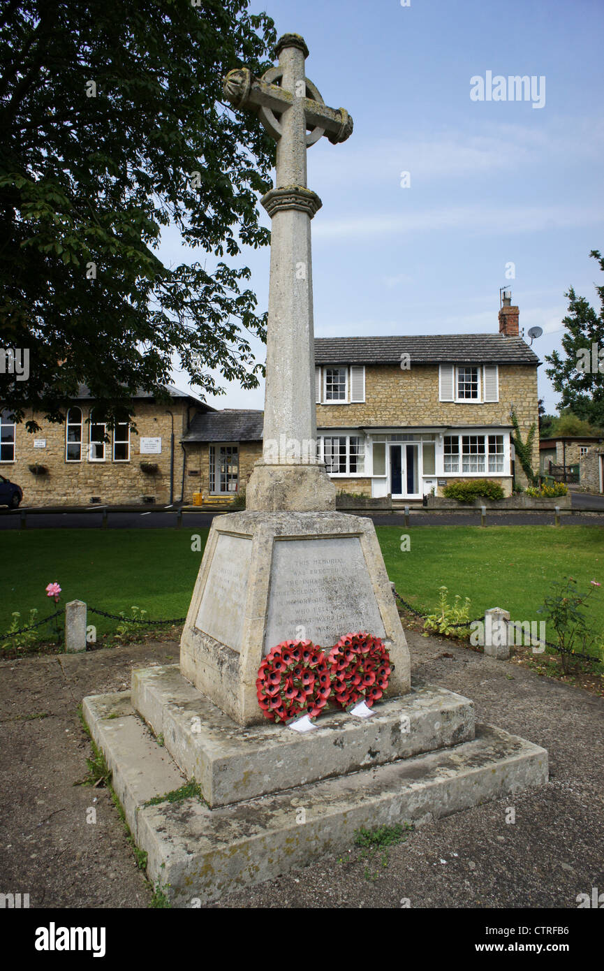 Stone war memorial on the village green at Stoke Goldington, Buckinghamshire - Stock Image