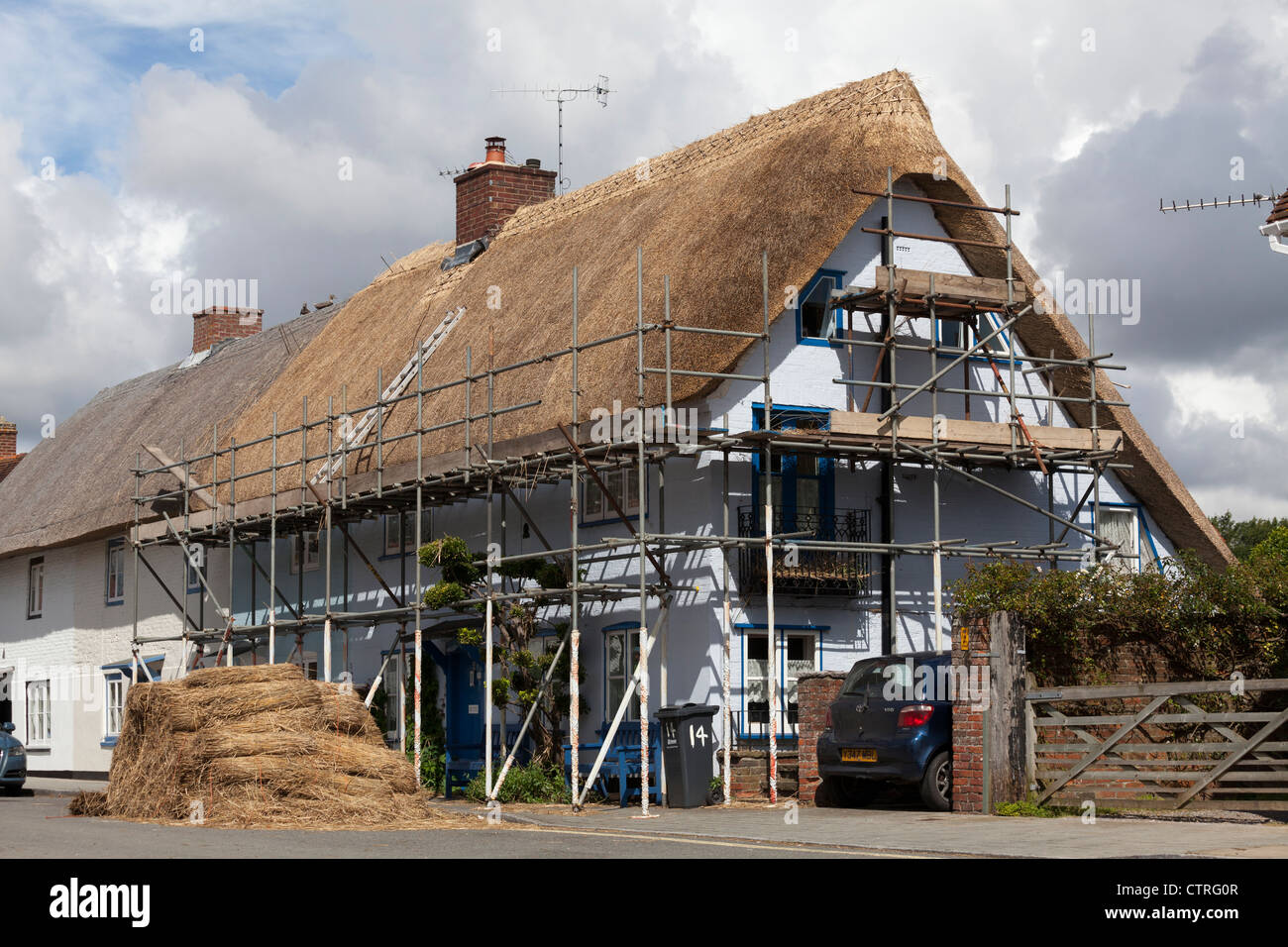 A thatched house in the process of being retached  with scaffold and stack of thatch waiting to be used - Stock Image