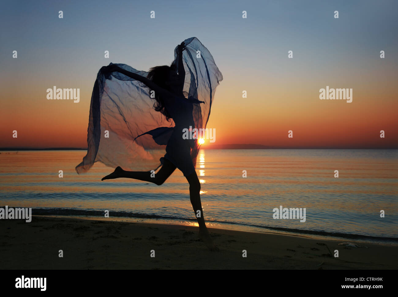 Elegant lady with fiber jumping and dancing at the morning beach during sunrise. Natural darkness and sunlight colors - Stock Image