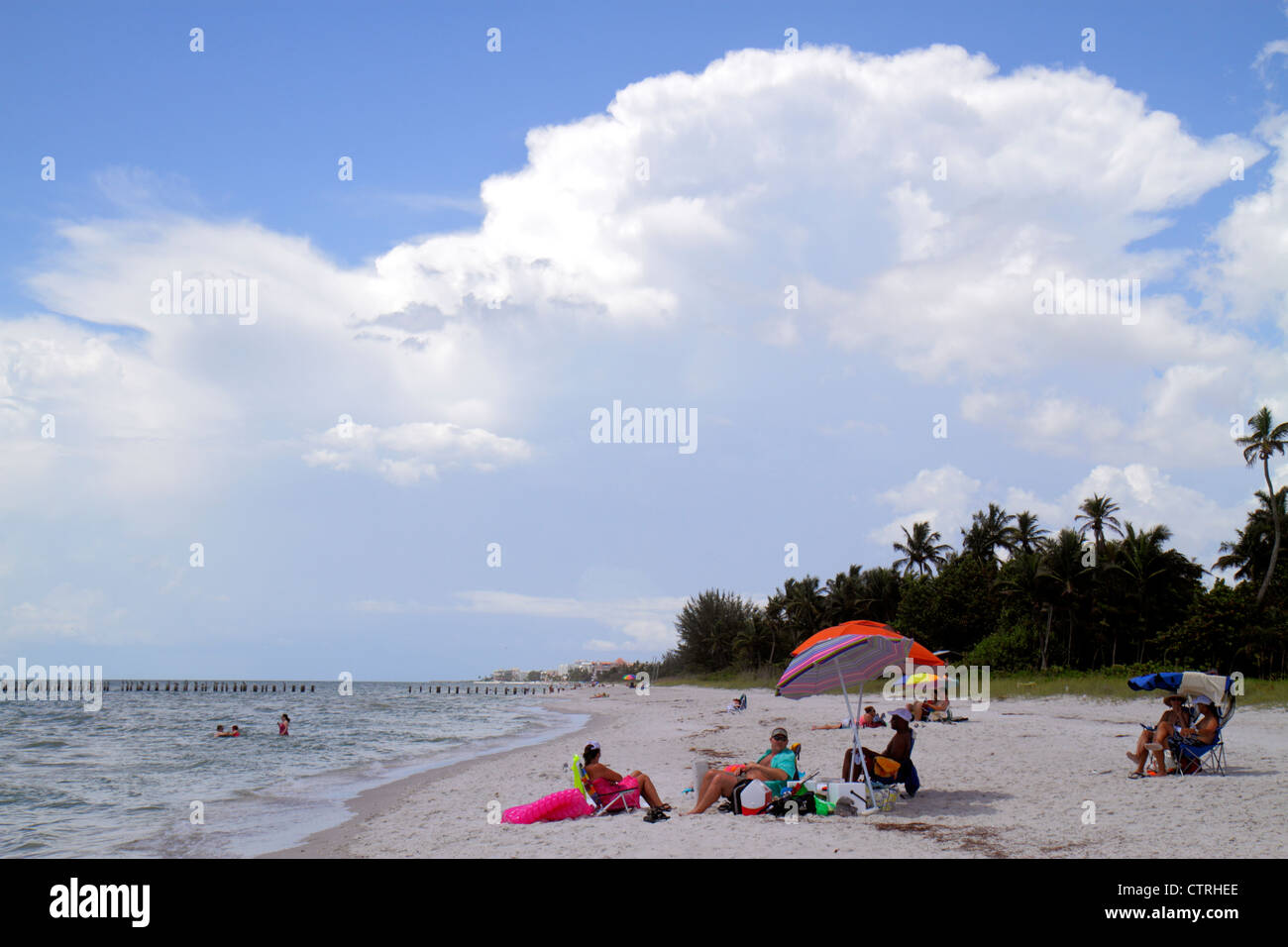 Naples Florida Gulf of Mexico public beach water waves surf sand sunbather clouds - Stock Image