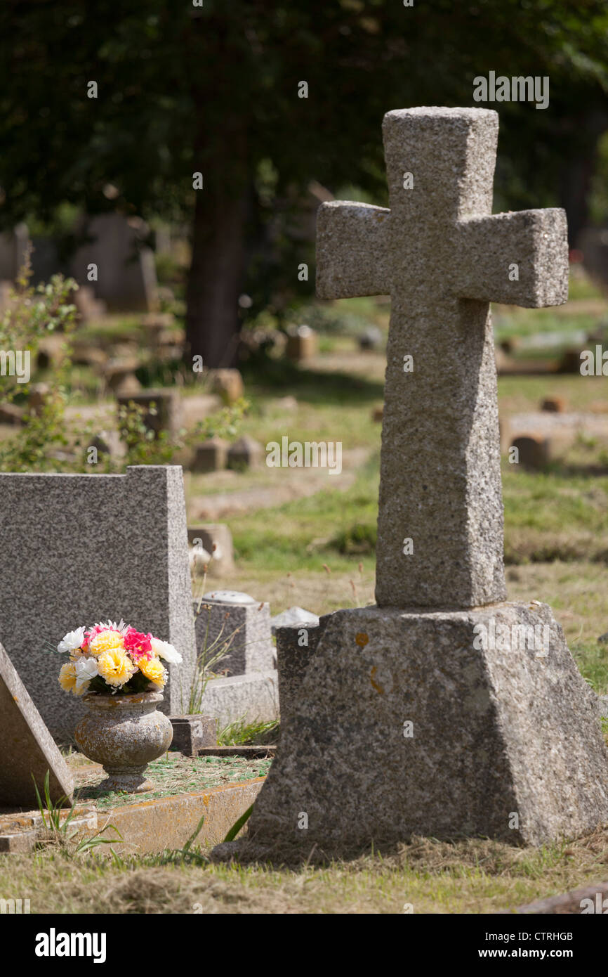 gravestone and flowers in a graveyard - Stock Image