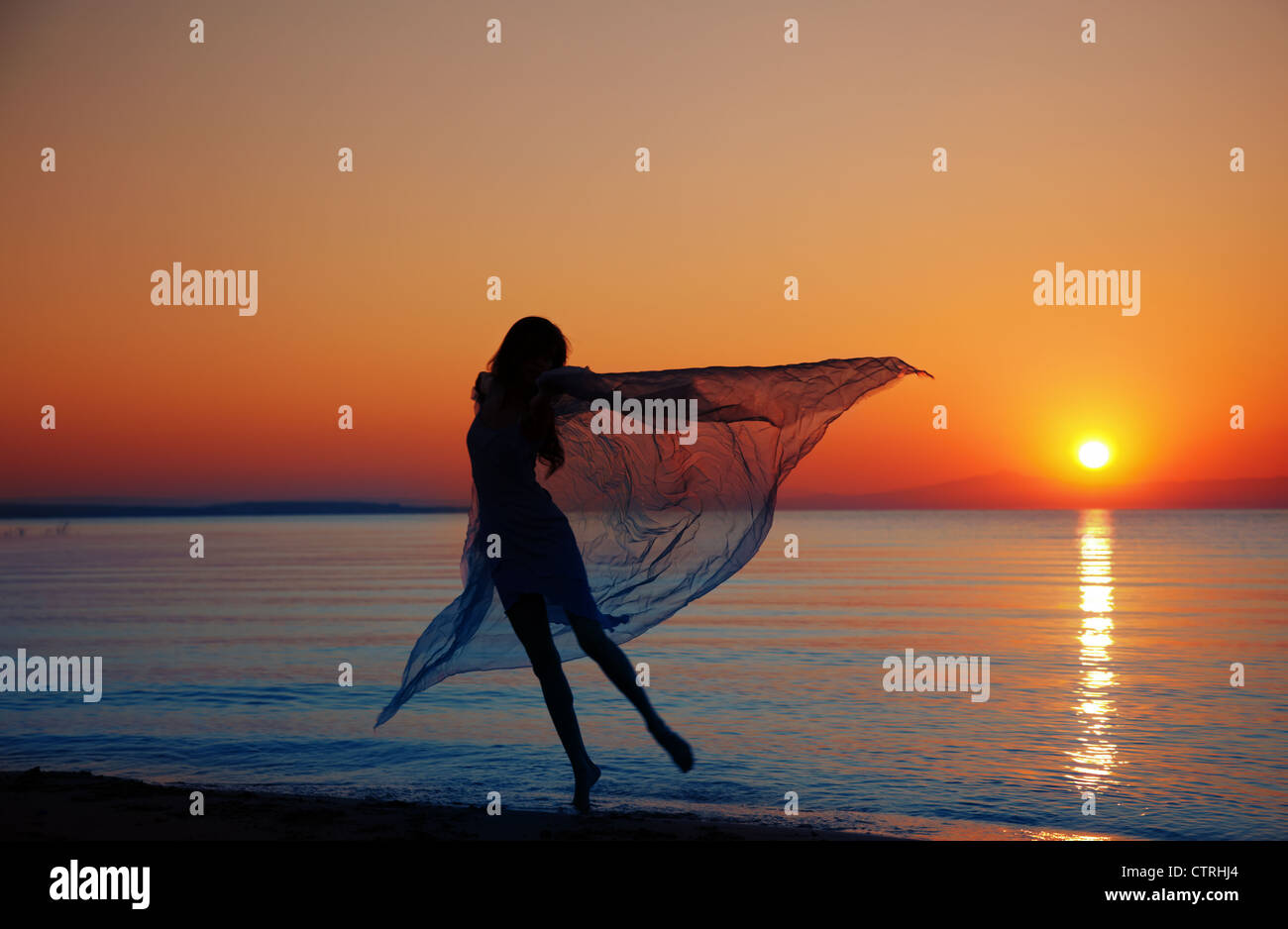 Silhouette of the nifty woman dancing at the sea during sunset. Natural light and darkness. Artistic colors added - Stock Image
