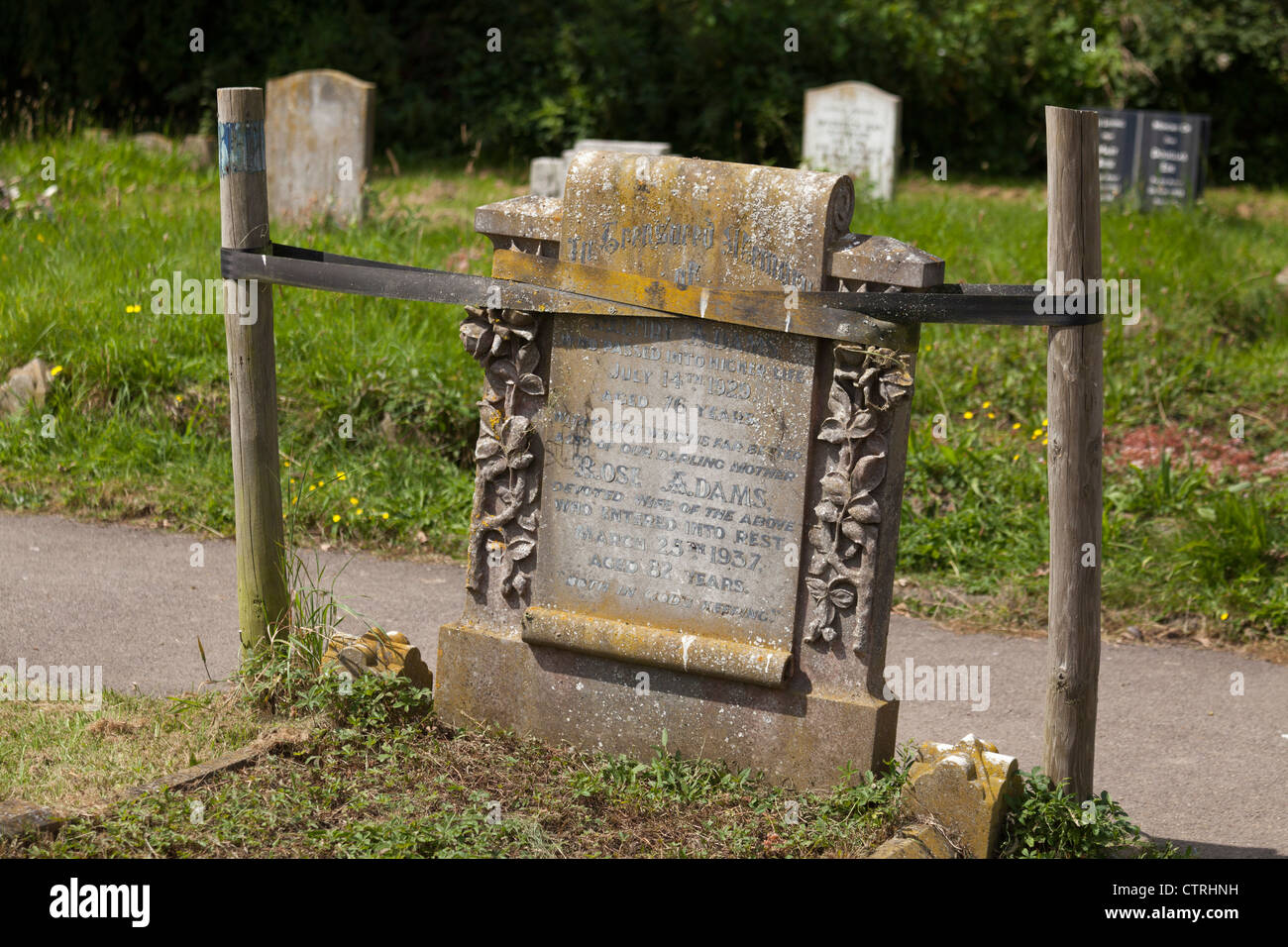 Gravestone headstone supported by starpping and wooden stakes in graveyard - Stock Image