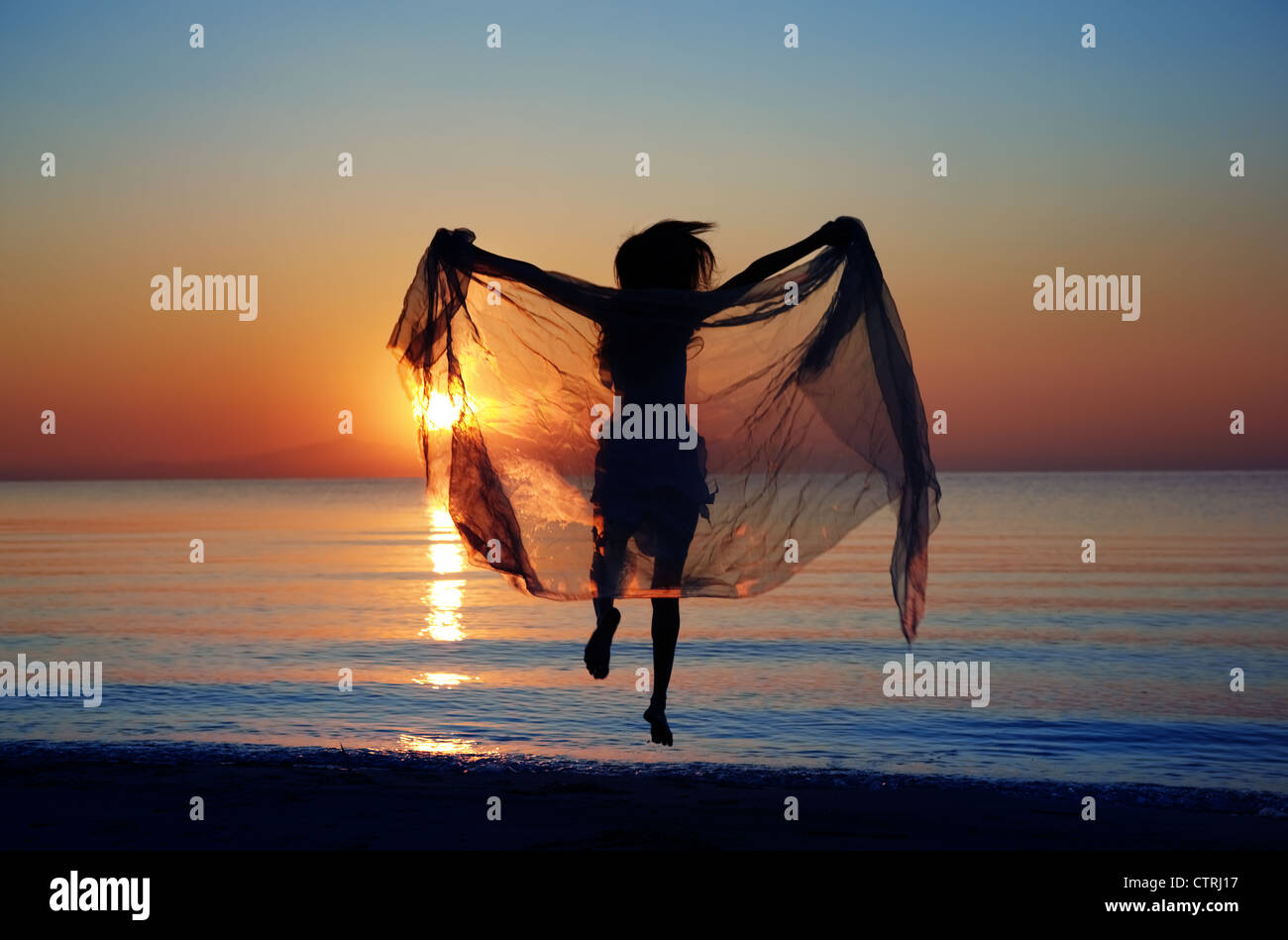 Rear view on the silhouette of the woman jumping at the beach during sunset. Natural darkness and colors - Stock Image