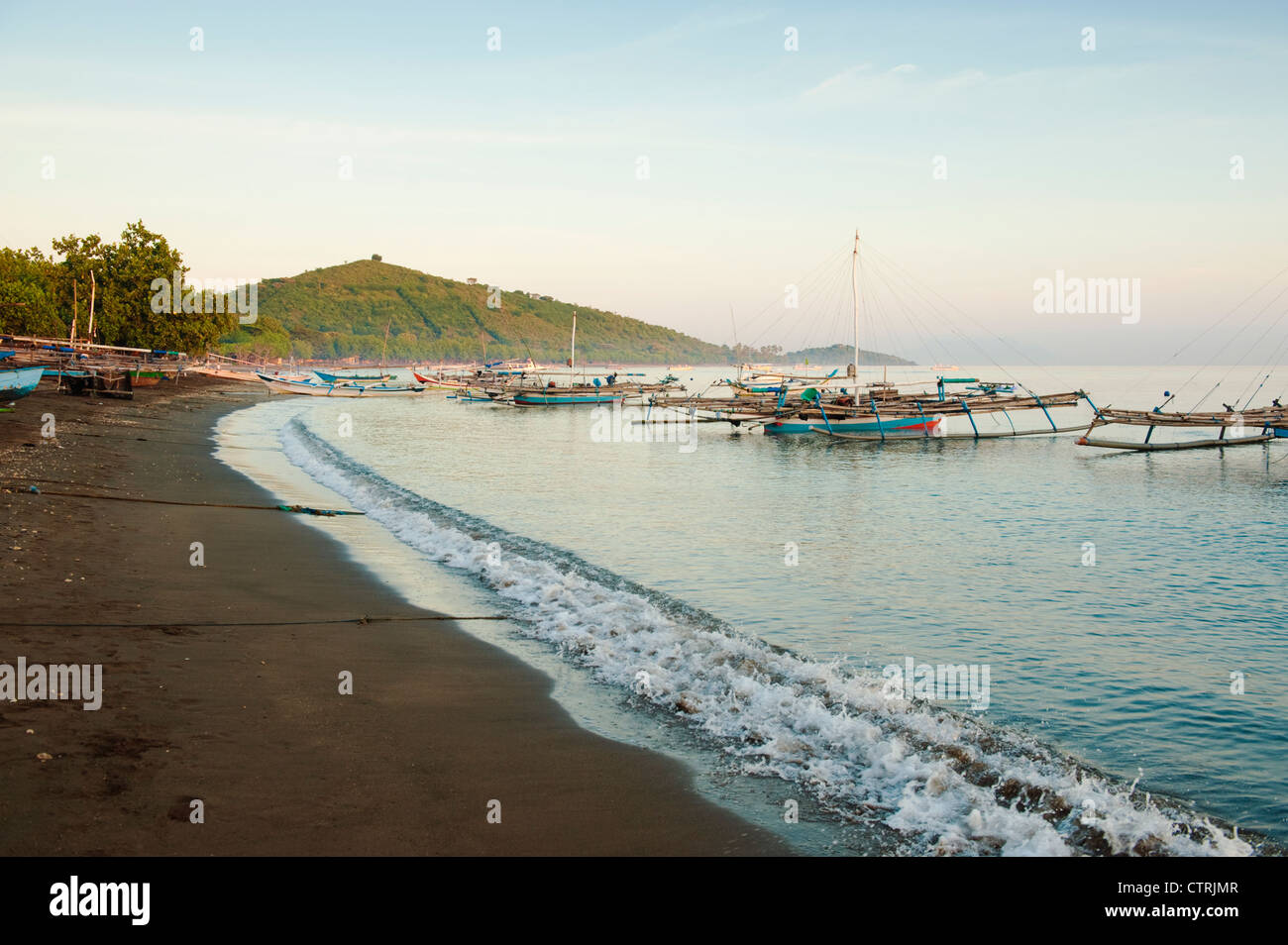 Balinese fishing boats anchor off the beach in the village of Pemuteran in north Bali, a destination for SCUBA and - Stock Image