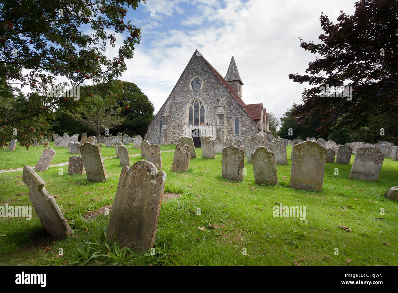 The 12C Church St Thomas à Becket, Warblington and gravestones in the churchyard. - Stock Image