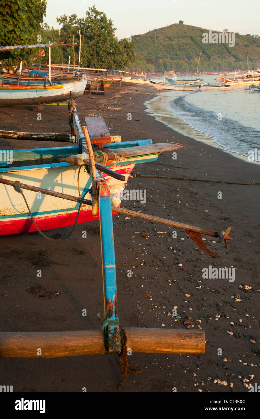 Traditional Balinese fishing boats line the beach waiting to go fishing in the village of Pemuteran in west Bali, - Stock Image