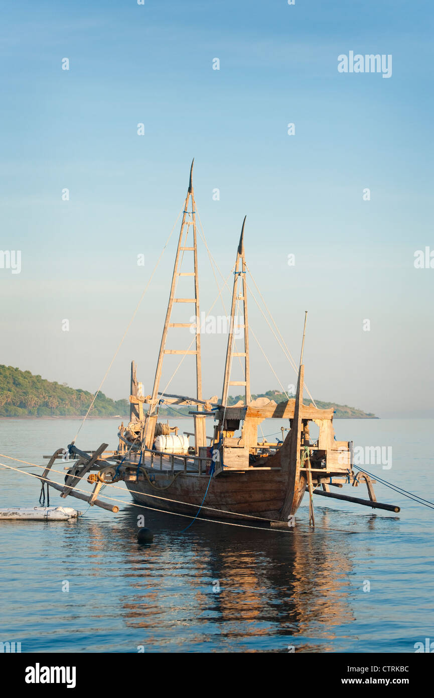 An exotic purse seine fishing boat called a Prahu Madura is docked in the fishing village of Pemuteran, Bali, Indonesia. - Stock Image