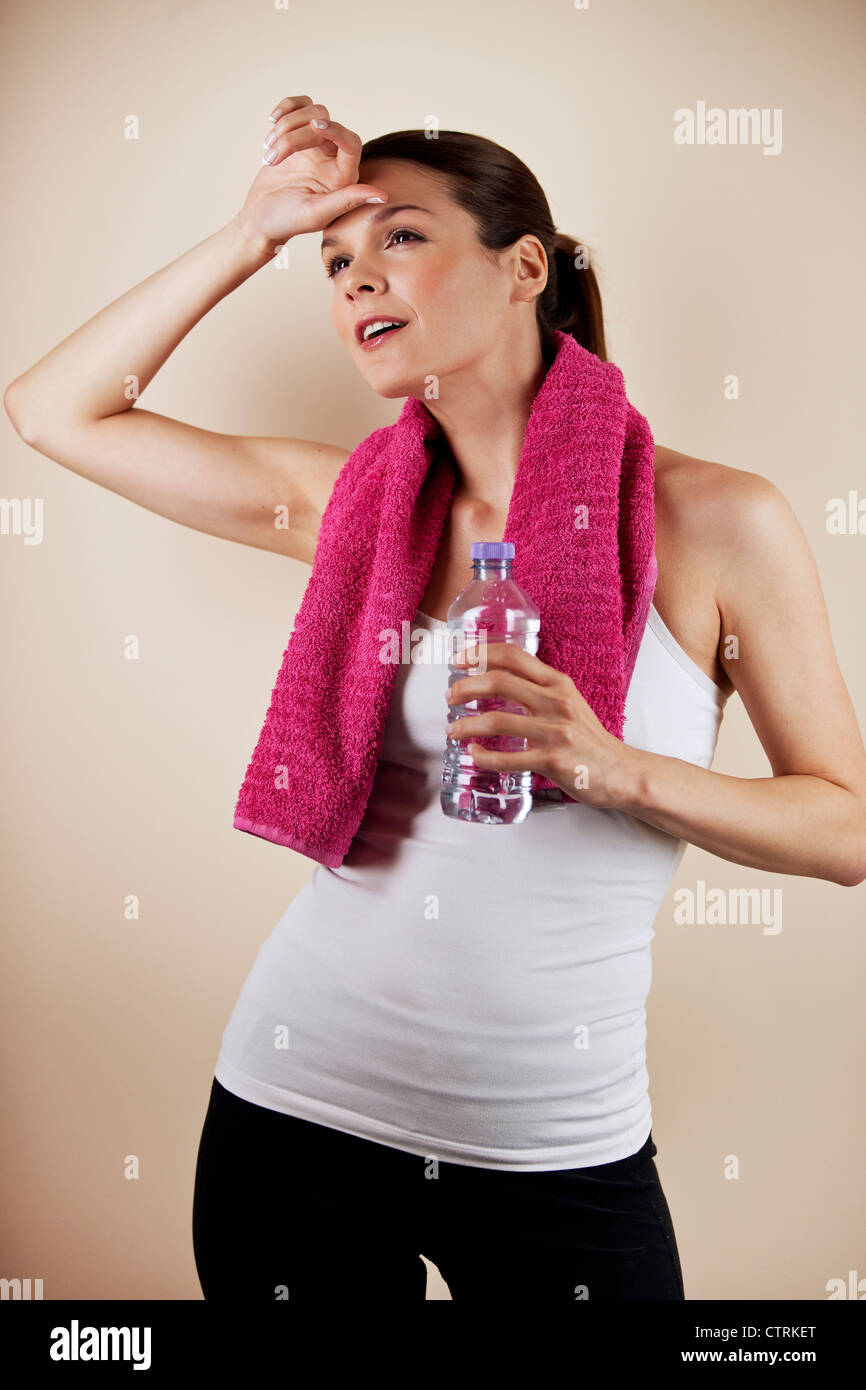 A young woman feeling hot, holding a towel and a bottle of water - Stock Image