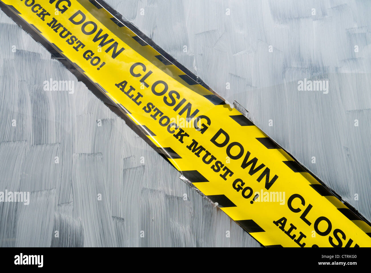 Closing down all stock must go yellow sign on a closed shop window. - Stock Image