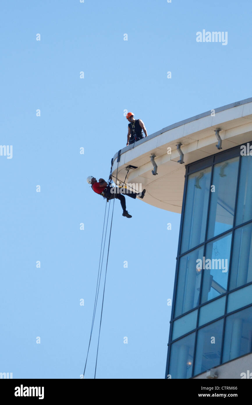 Maintenance workers in abseil harness's work on Swansea's new Meridian Tower in the marina. - Stock Image