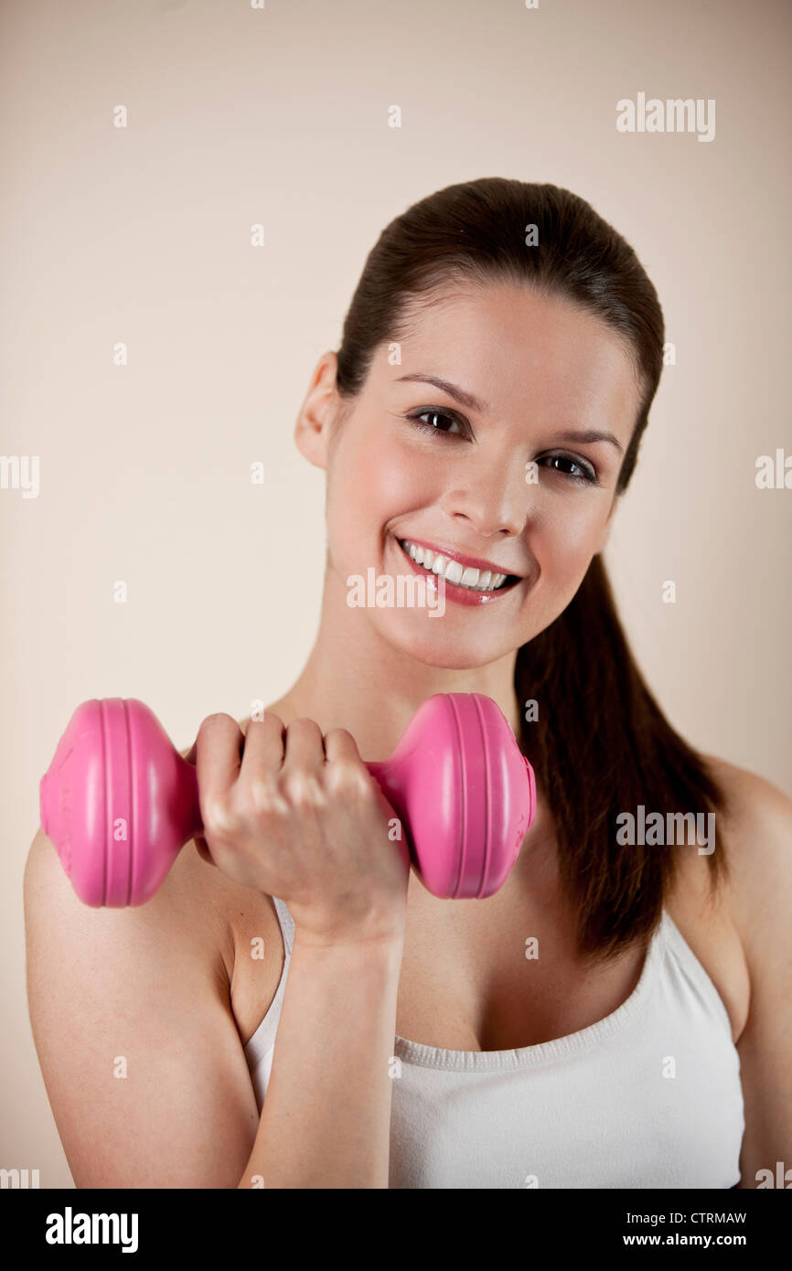 A young woman holding a pink dumbbell, smiling to camera - Stock Image