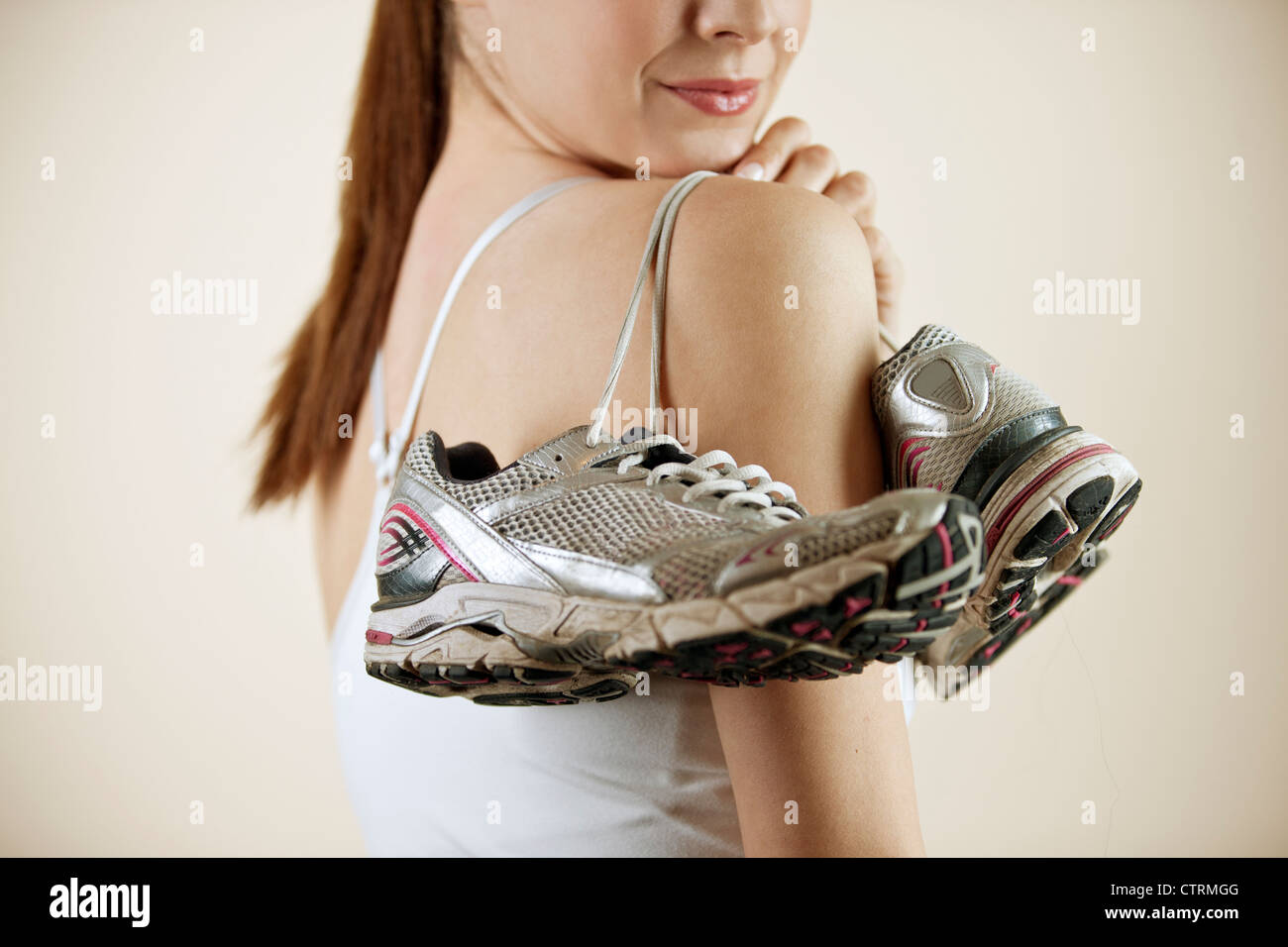 A young woman holding a pair of training shoes over her shoulder, close-up Stock Photo