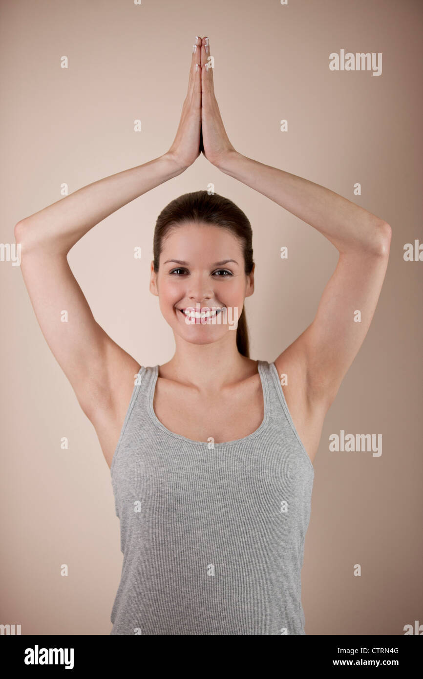 A young woman practicing yoga, tree pose - Stock Image