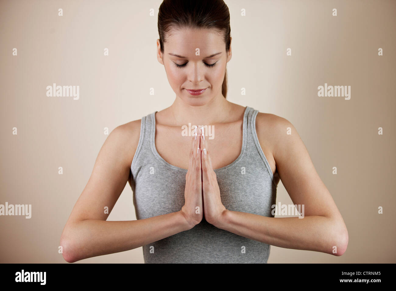 A young woman meditating, hands in prayer position - Stock Image
