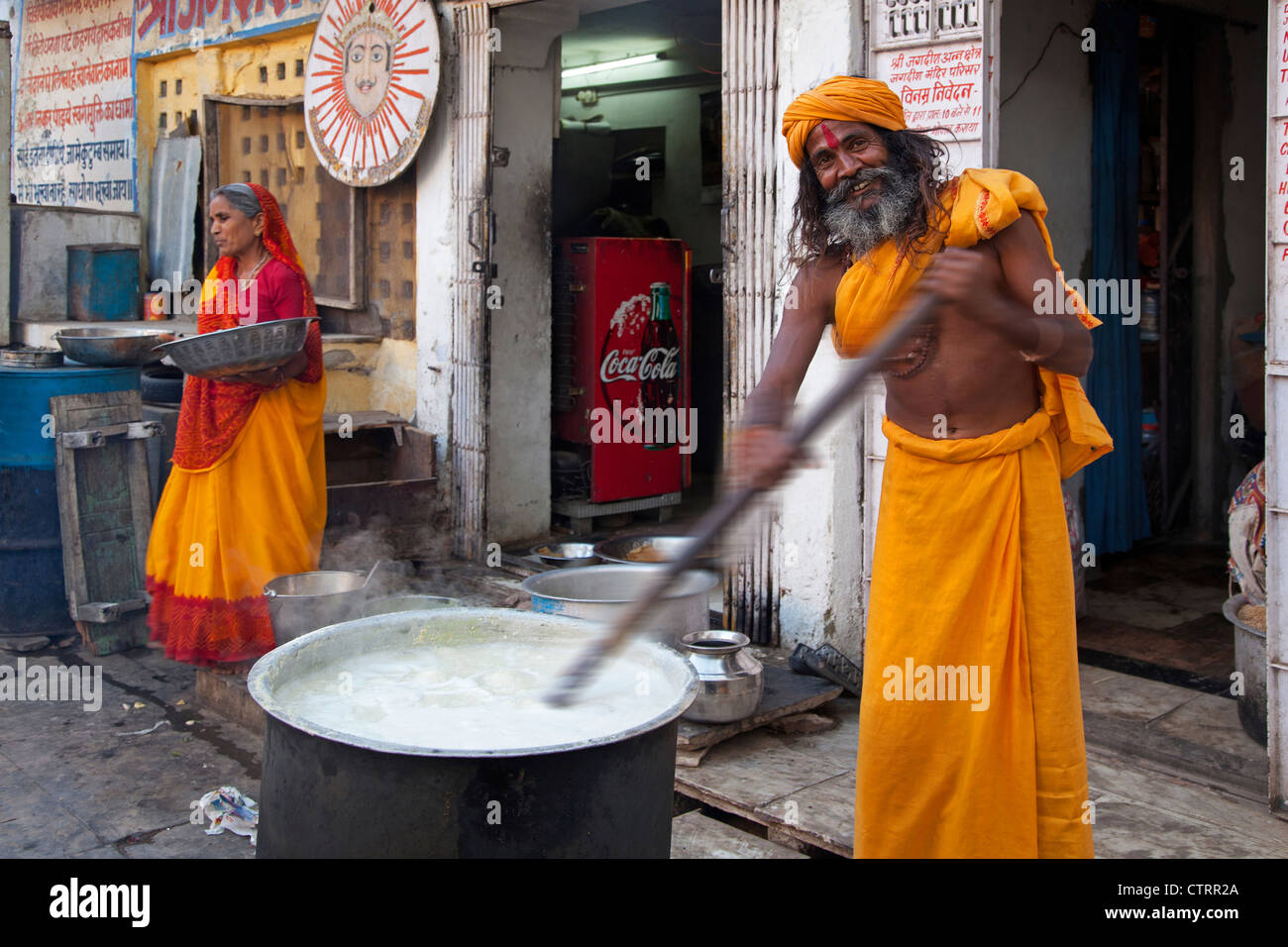Hindu man wearing red bindi on forehead stirring food in huge pot for the needy in Udaipur, Rajasthan, India - Stock Image
