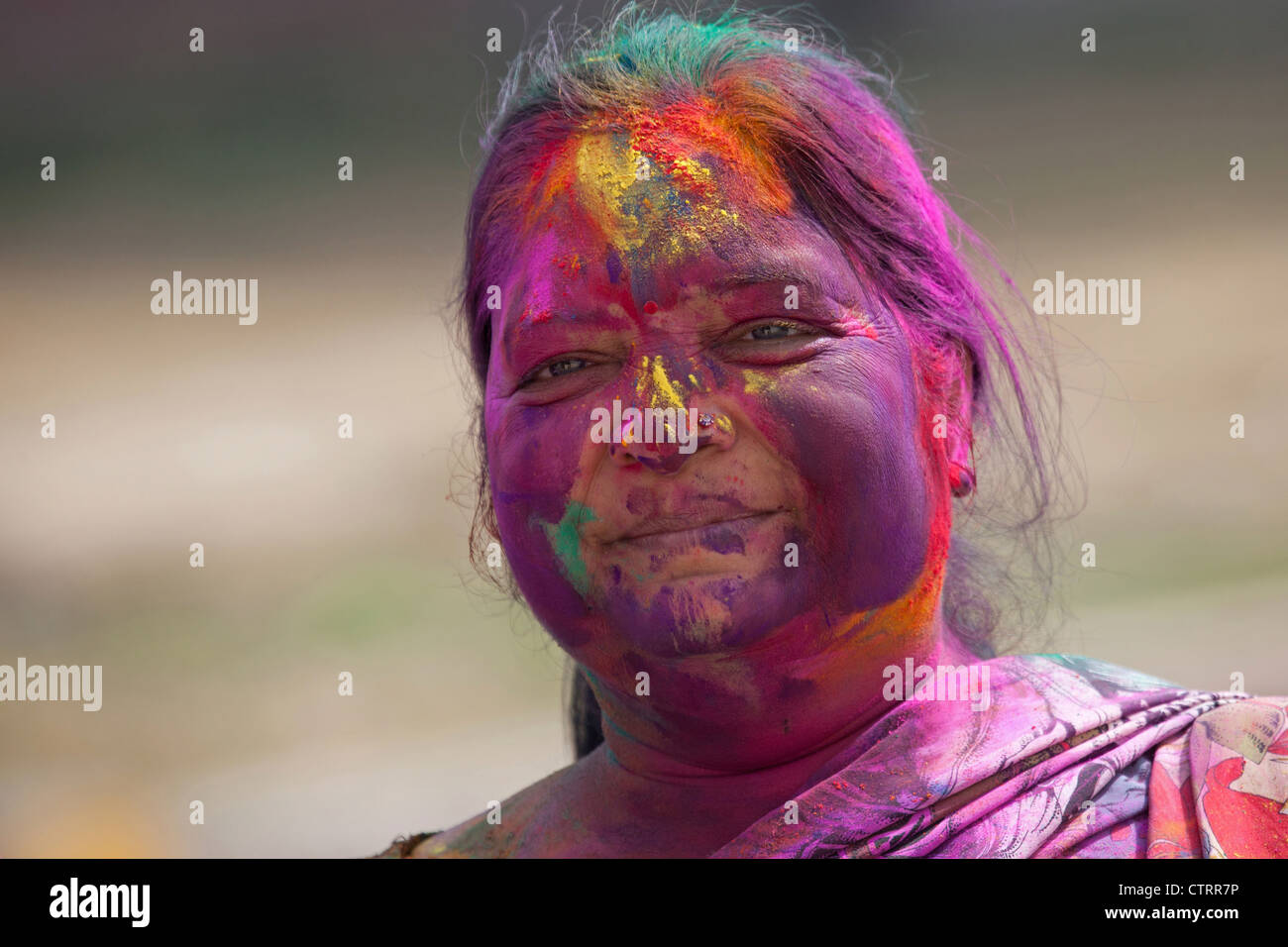 Woman covered in colourful dye celebrating the Holi festival, Festival of Colours in Mathura, Uttar Pradesh, India - Stock Image