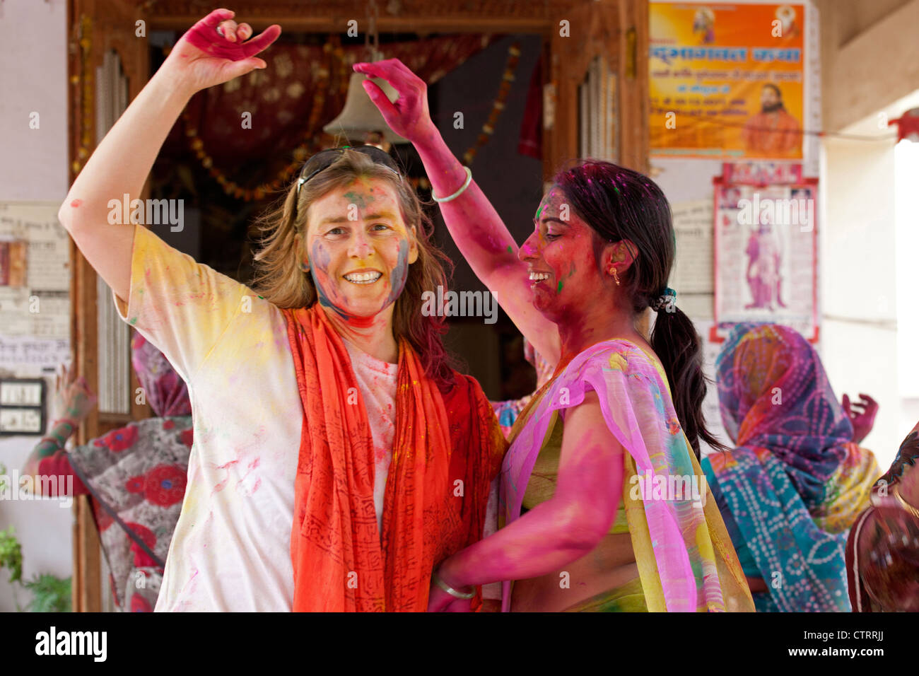 Tourist and Indian women colourfully dyed celebrating the Holi festival, Festival of Colours in Mathura, Uttar Pradesh, - Stock Image