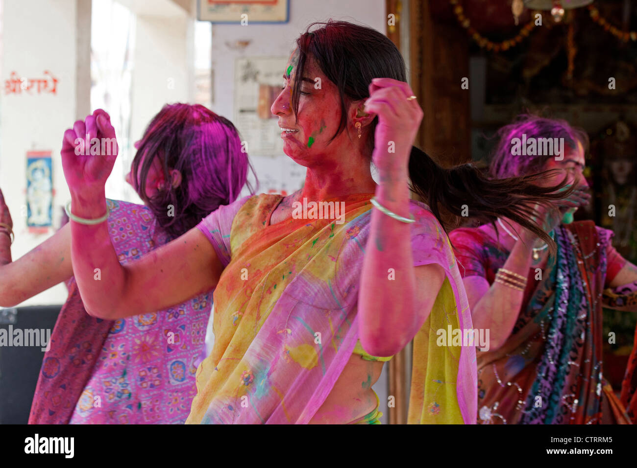 Women covered in colourful dye celebrating the Holi festival, Festival of Colours in Mathura, Uttar Pradesh, India - Stock Image