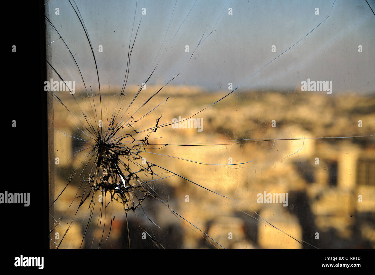 Broken window, cracked glass on urbanic background - Stock Image