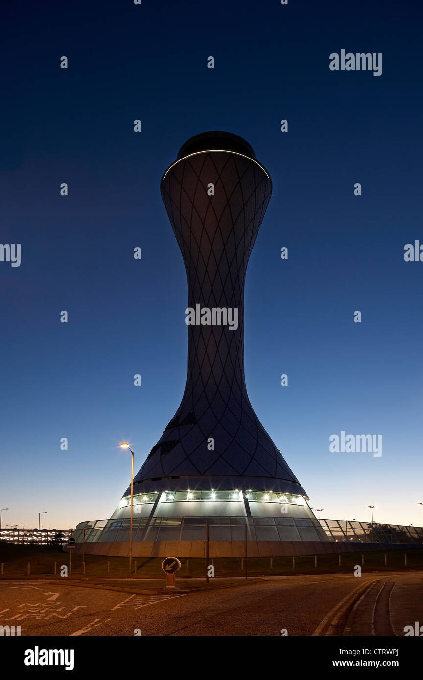 air traffic control tower dawn view lit from approach road - Stock Image