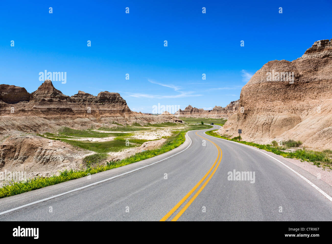 Distant car on the Loop road through Badlands National Park, South Dakota, USA - Stock Image