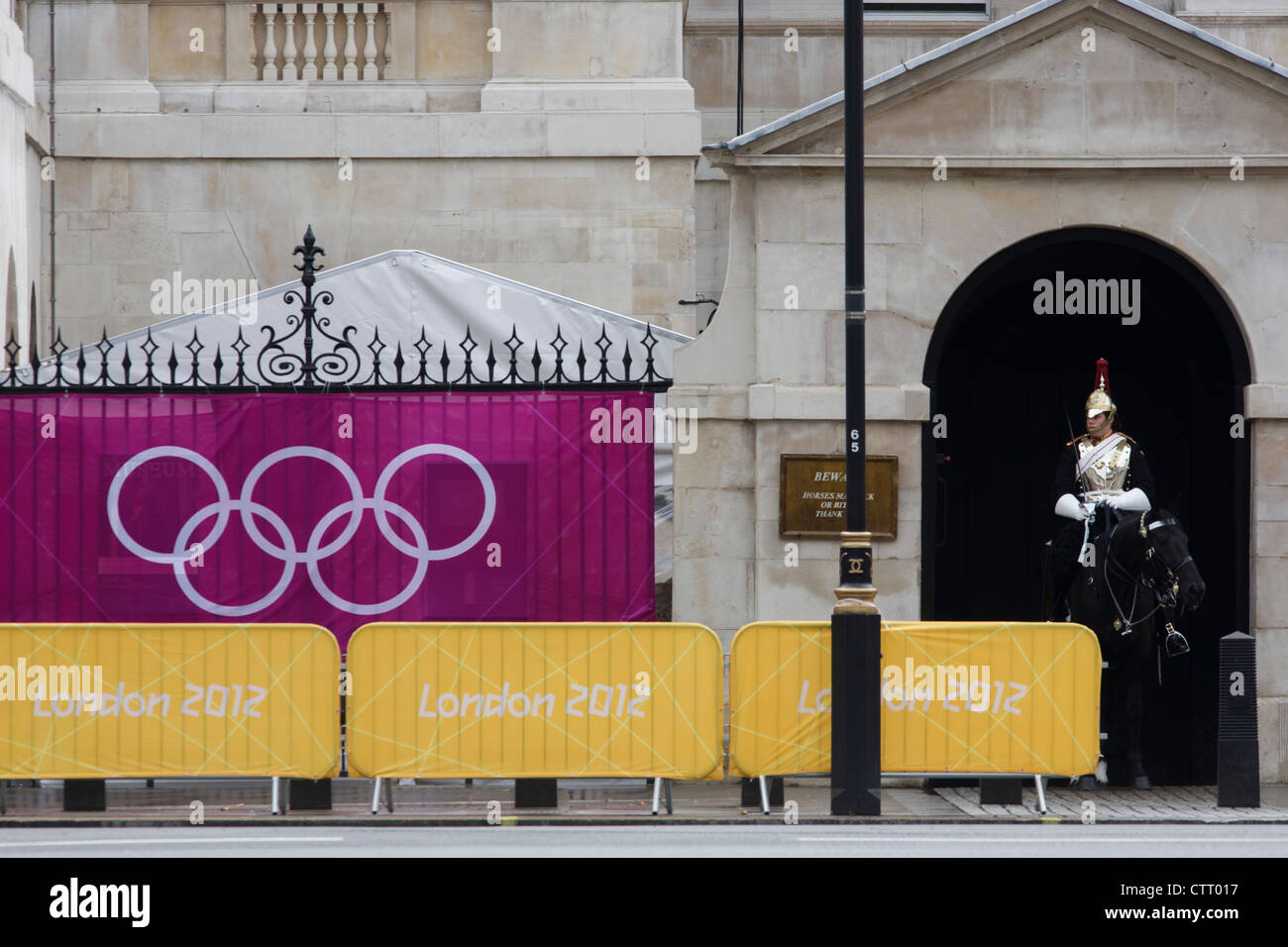 Olympic rings on a banner outside Horse Guards where a soldier from the Household Cavalry sits motionless on his Stock Photo