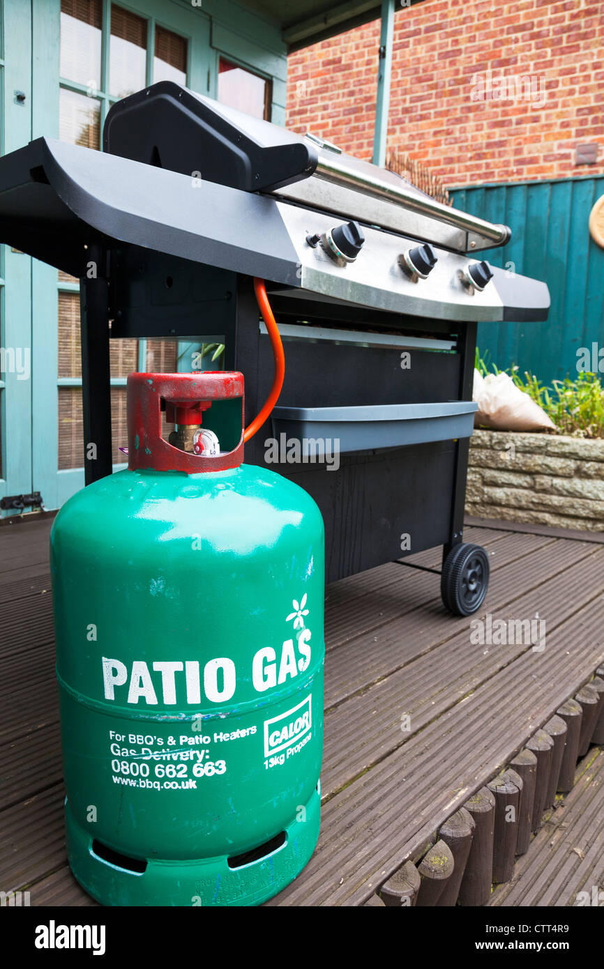 Green cylinder propane calor patio Gas Cylinder bottle & barbecue on patio - Stock Image