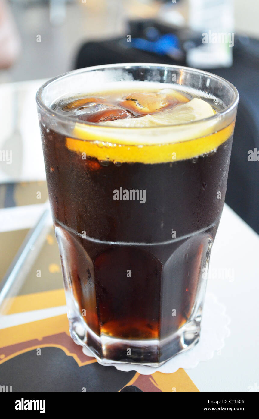 A pint glass filled with cola, ice and lemon - Stock Image
