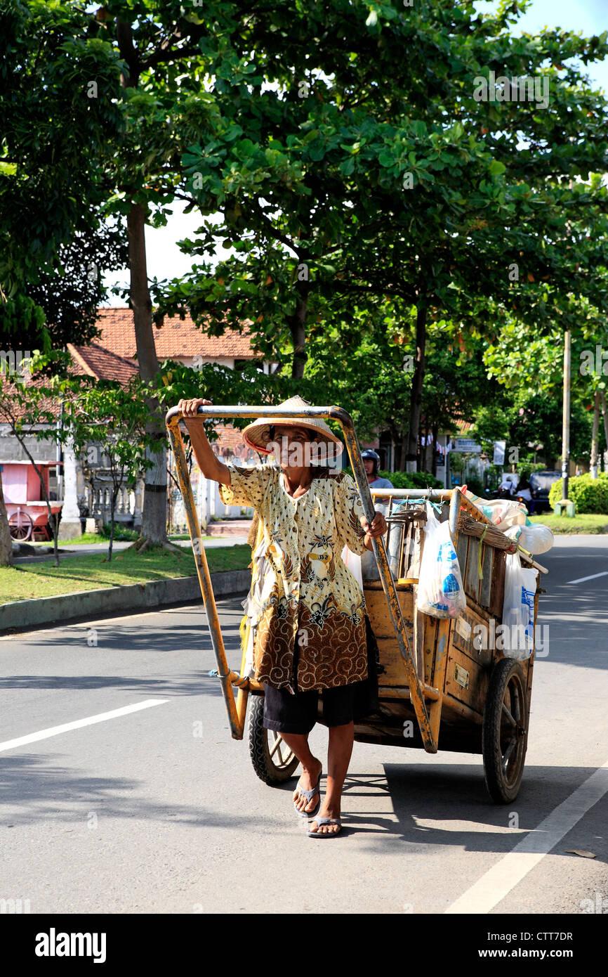 Female street cleaner, pulling her cart, Singaraja, north Bali, Indonesia. - Stock Image