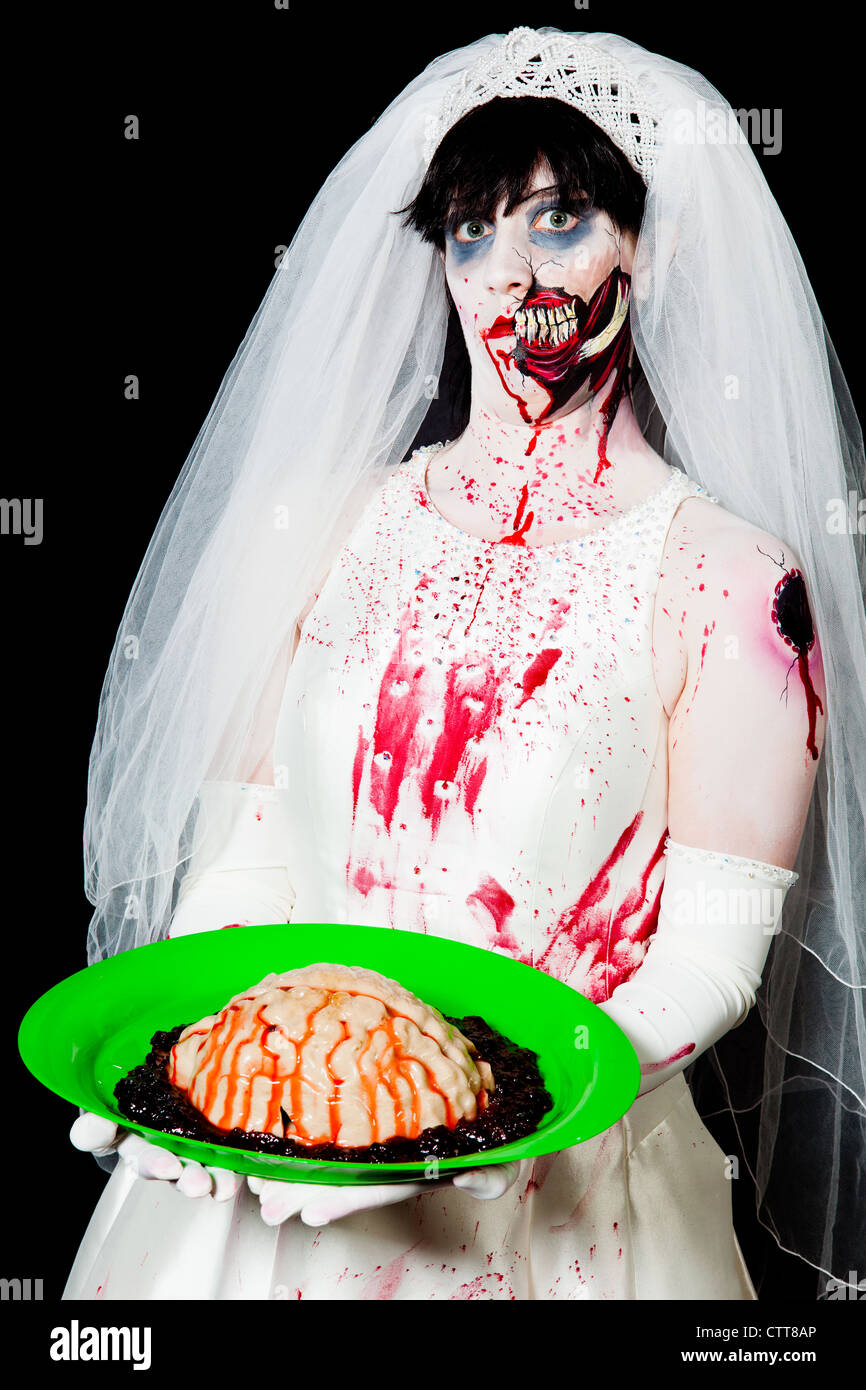 A zombie bride prepares to serve brains to her groom - Stock Image