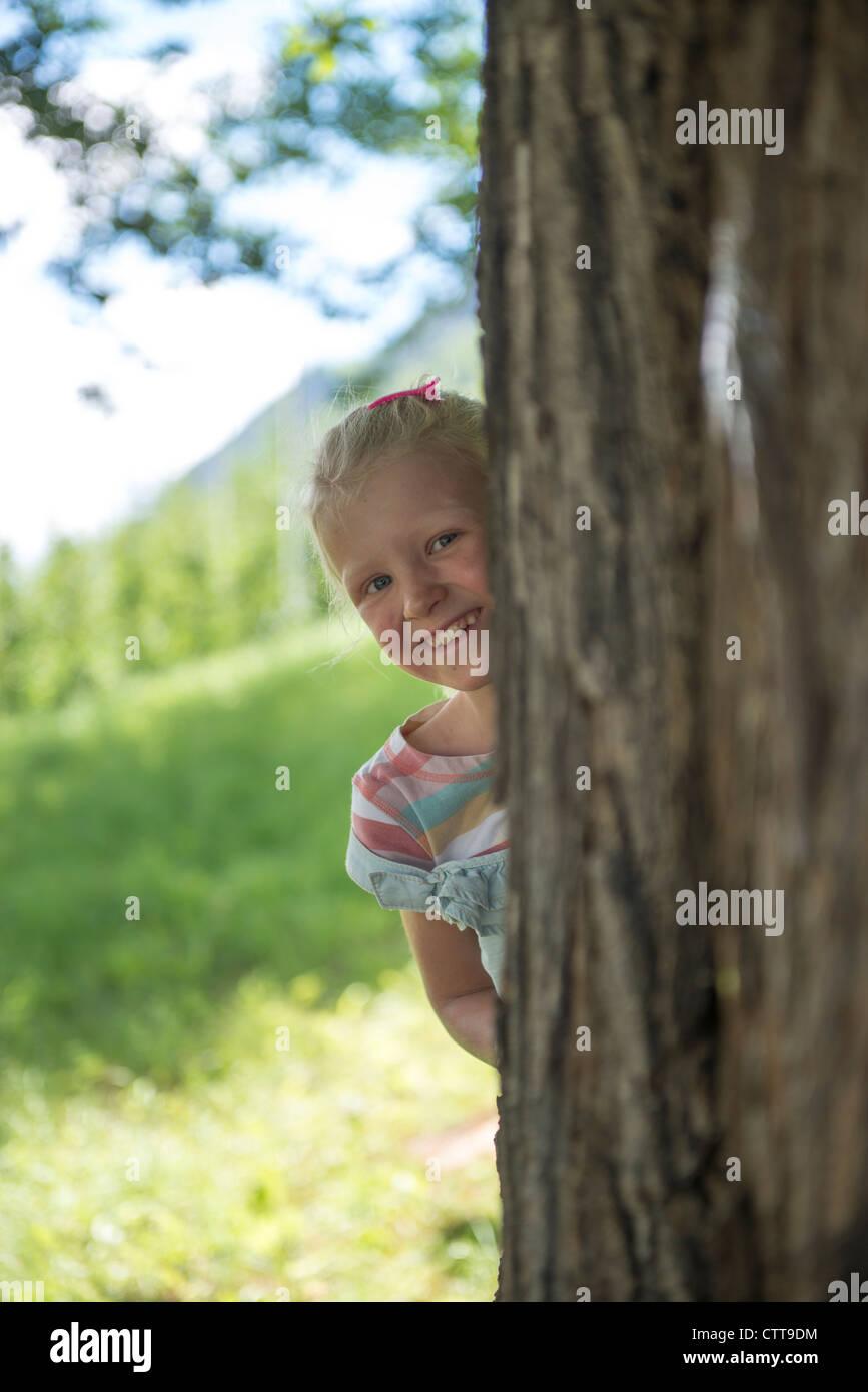 Girl looking out behind tree Mädchen schaut hinter Baum heraus - Stock Image