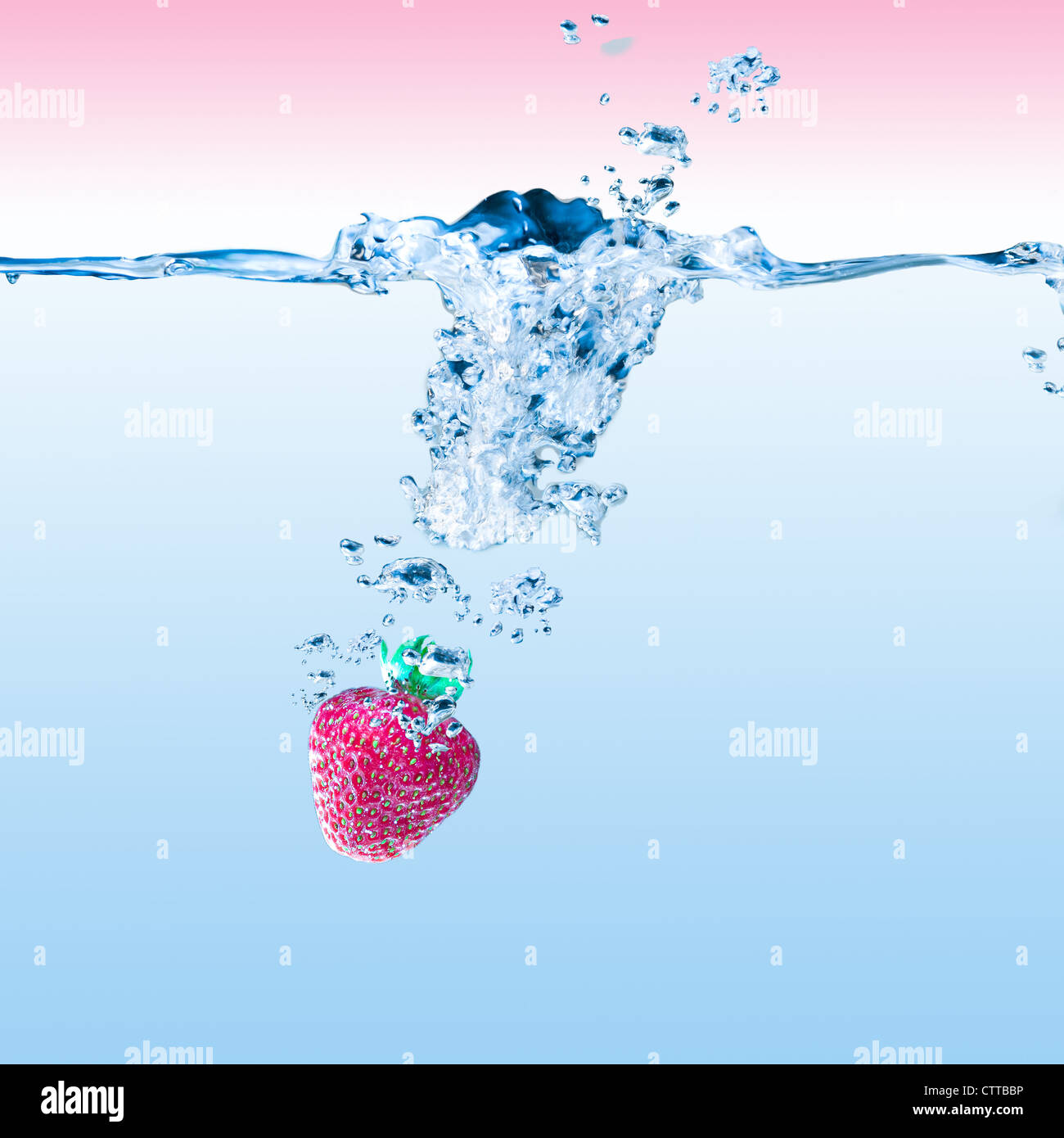close-up shot of a strawberry in the splashing water - Stock Image